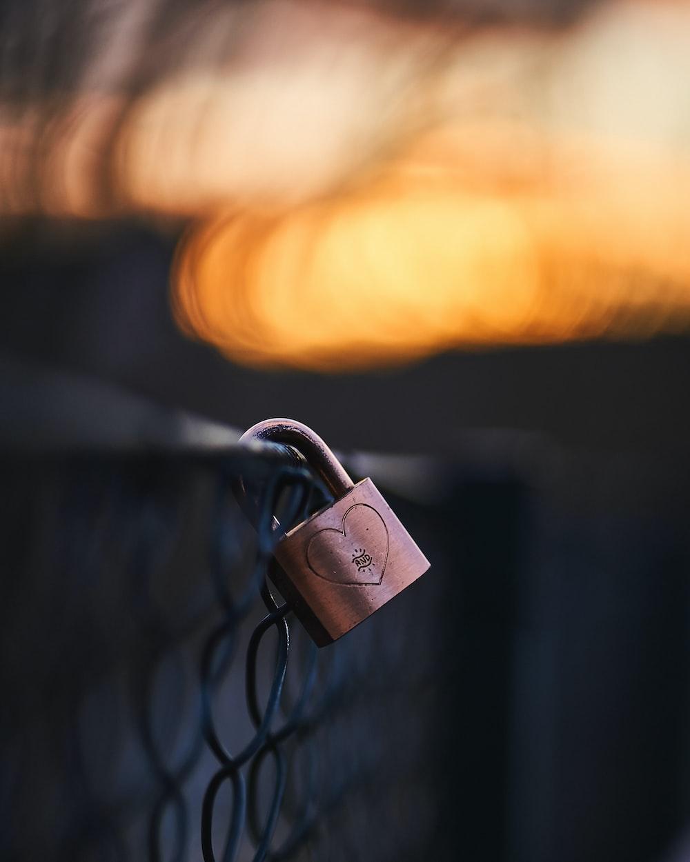 brown padlock on black metal fence
