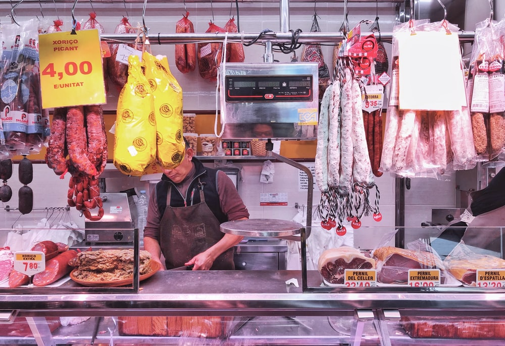 woman in black jacket standing in front of food display counter