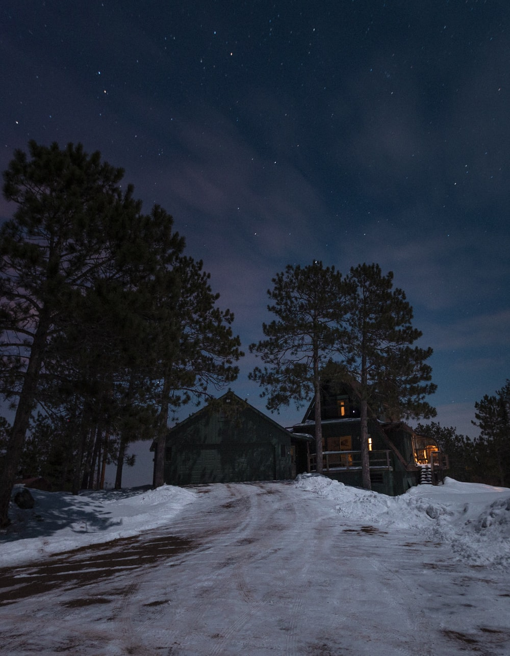 brown wooden house in the middle of snow covered field during night time