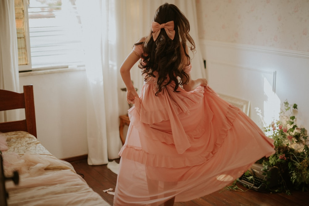woman in pink dress standing on bed