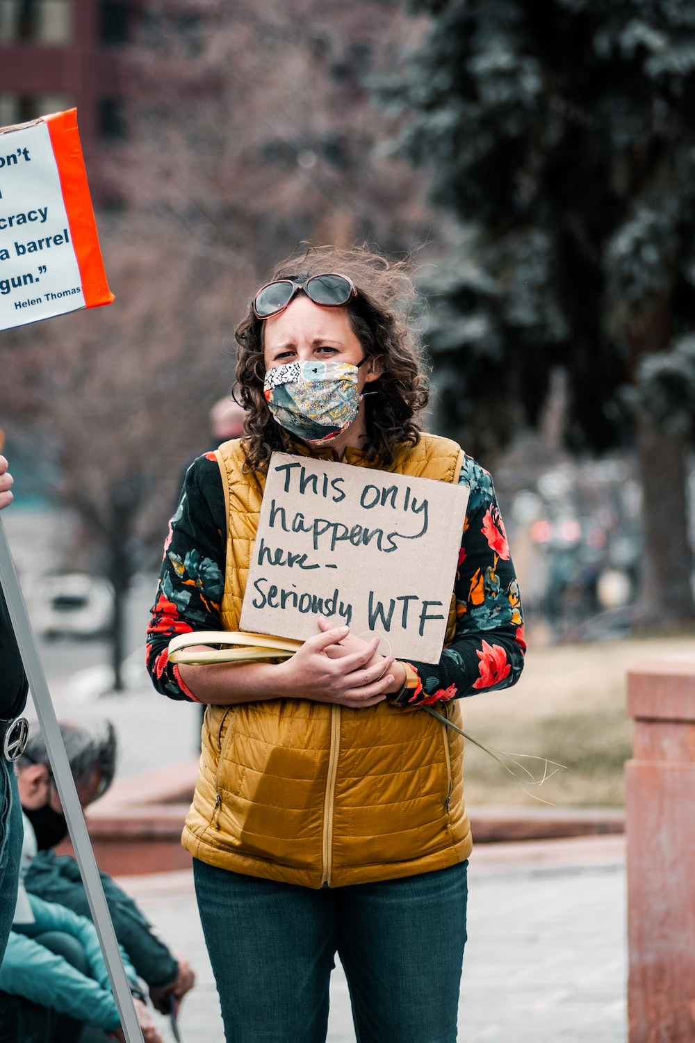 woman in yellow and blue jacket holding white and red signage