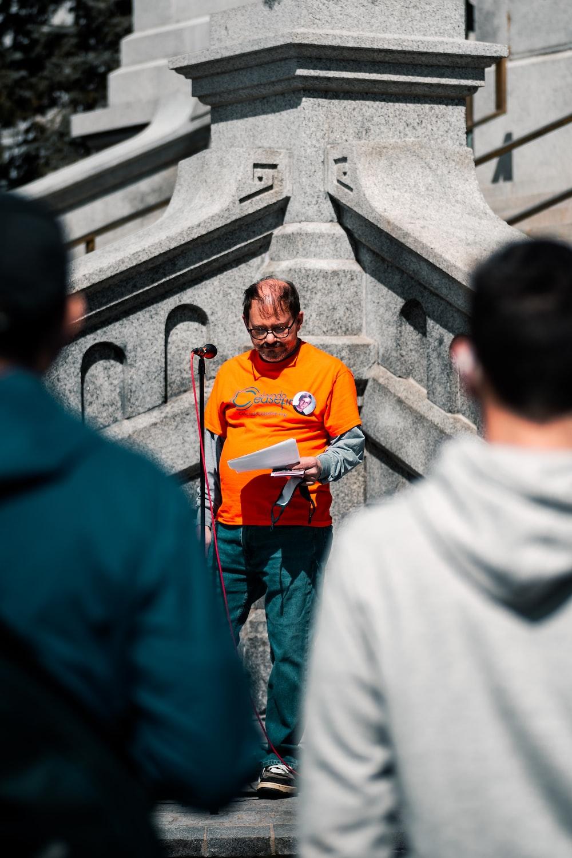man in orange crew neck t-shirt standing beside woman in white hijab