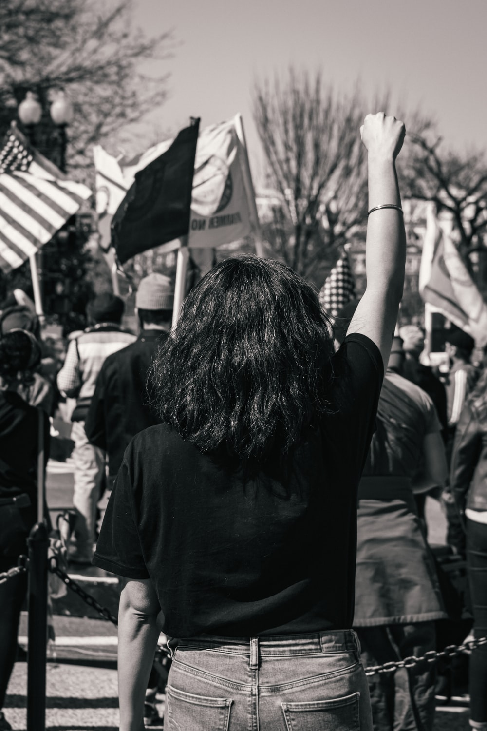 grayscale photo of woman in black shirt holding flag