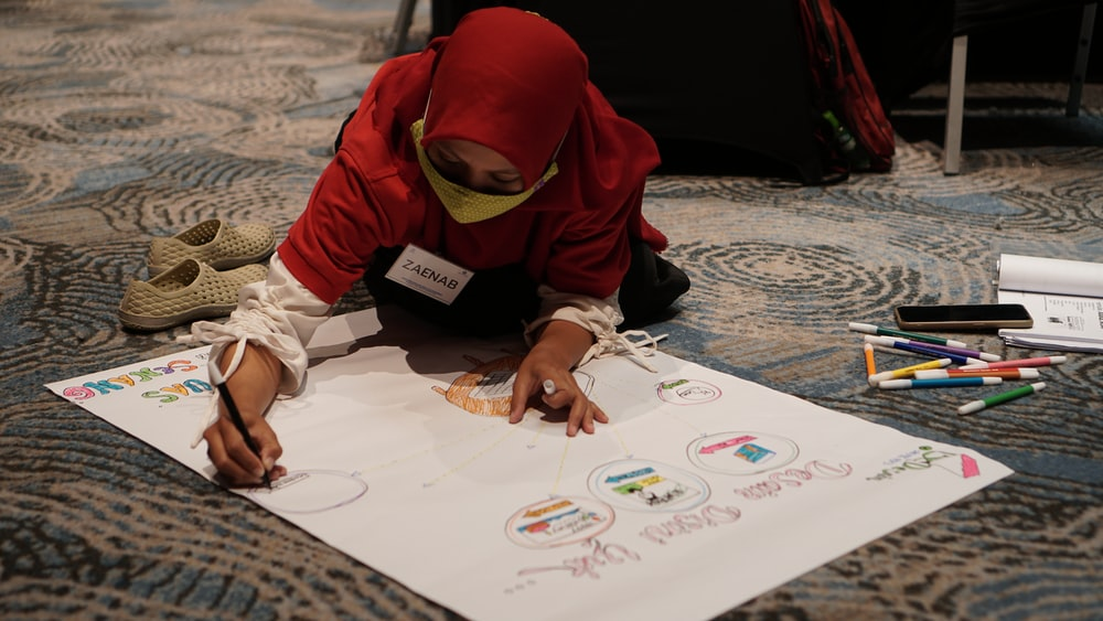 child in red knit cap and white long sleeve shirt writing on white paper