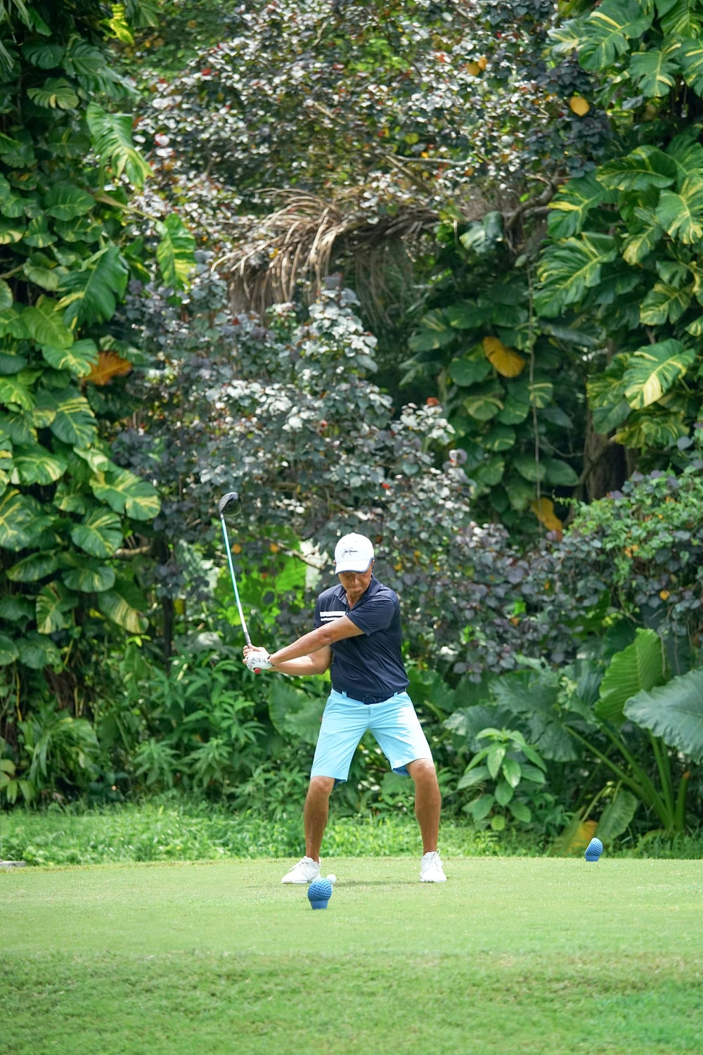 man in blue shirt and brown shorts playing golf during daytime