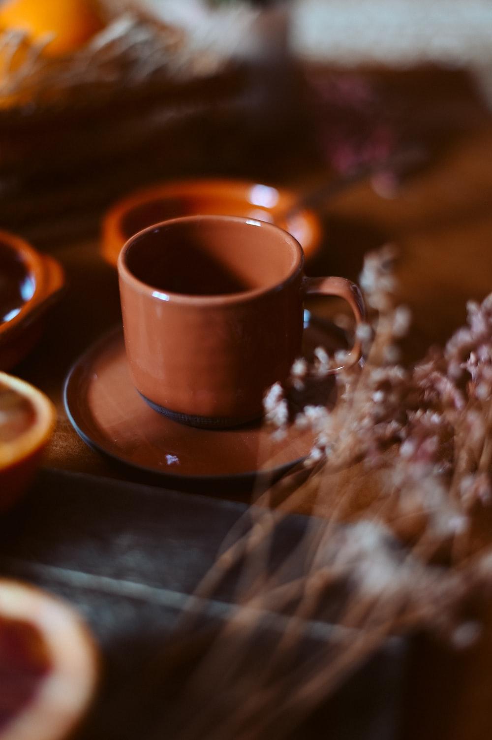 brown ceramic mug on brown saucer
