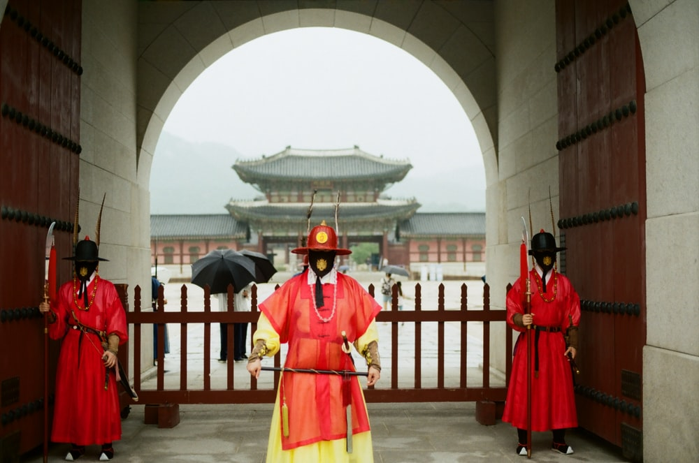 people in red and yellow traditional dress standing on gray concrete floor during daytime