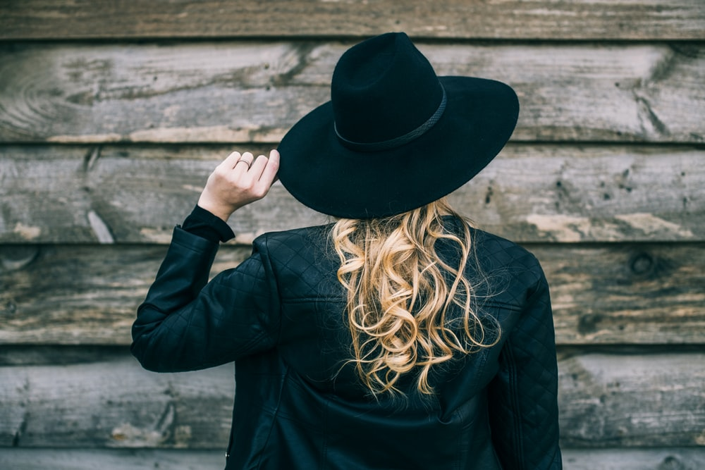 woman in black long sleeved shirt and black hat