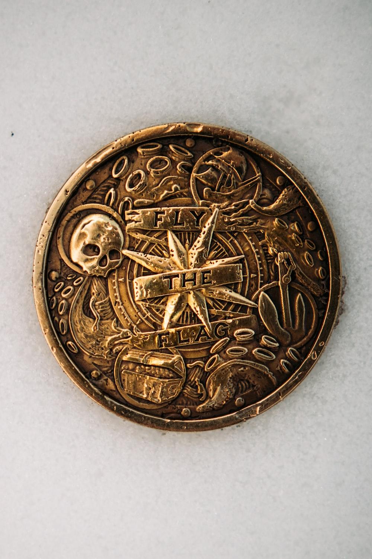 gold round coin on white textile