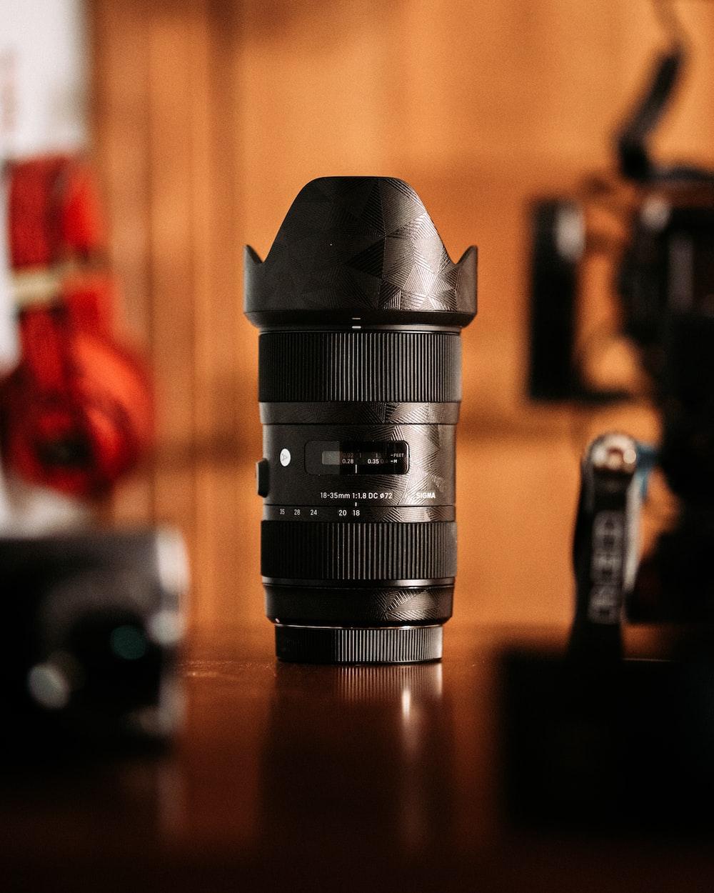 black dslr camera lens on brown wooden table