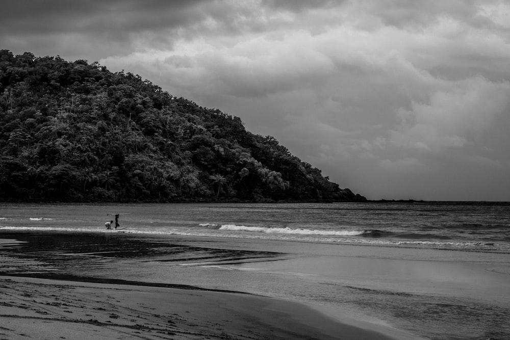grayscale photo of 2 people walking on beach