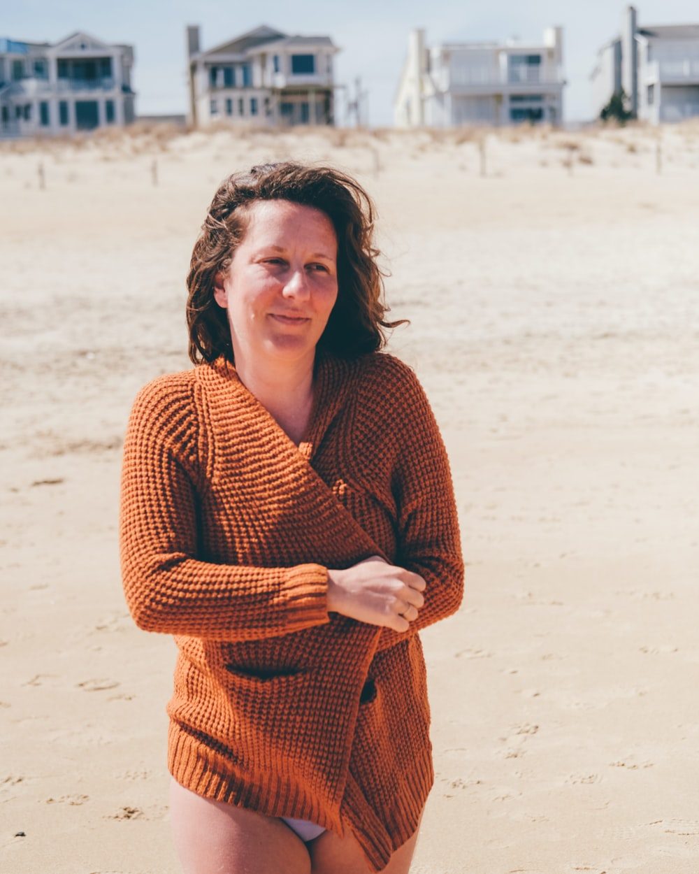 woman in red knit sweater standing on beach during daytime