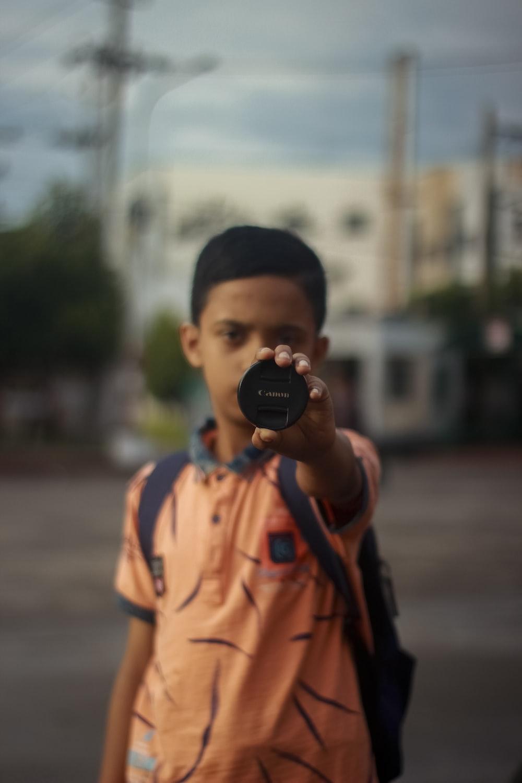 boy in orange and black jacket holding black camera