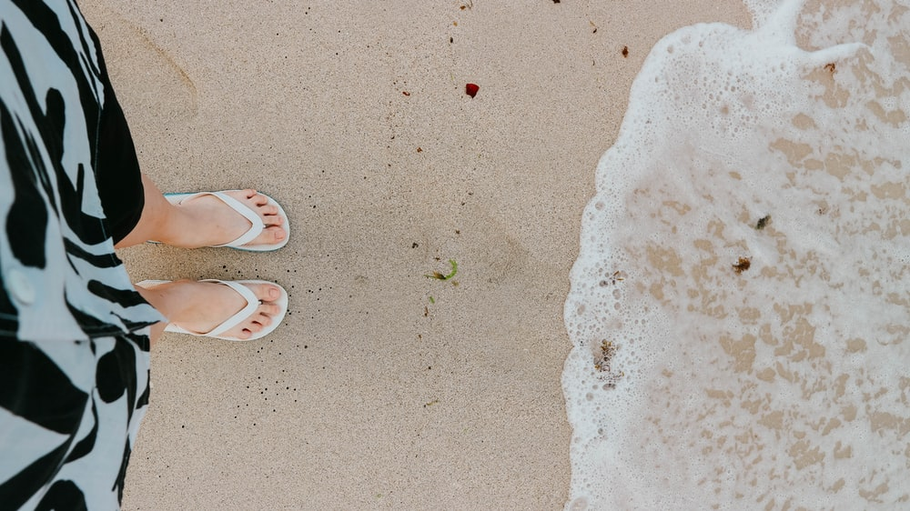 person wearing brown flip flops standing on white sand beach during daytime