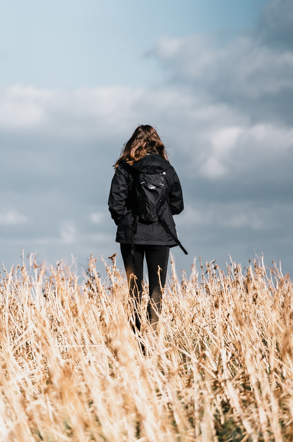 woman in black coat standing on brown grass field during daytime