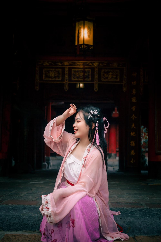 woman in pink dress sitting on floor
