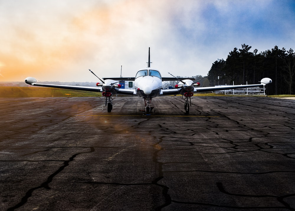 white airplane on brown field under gray clouds