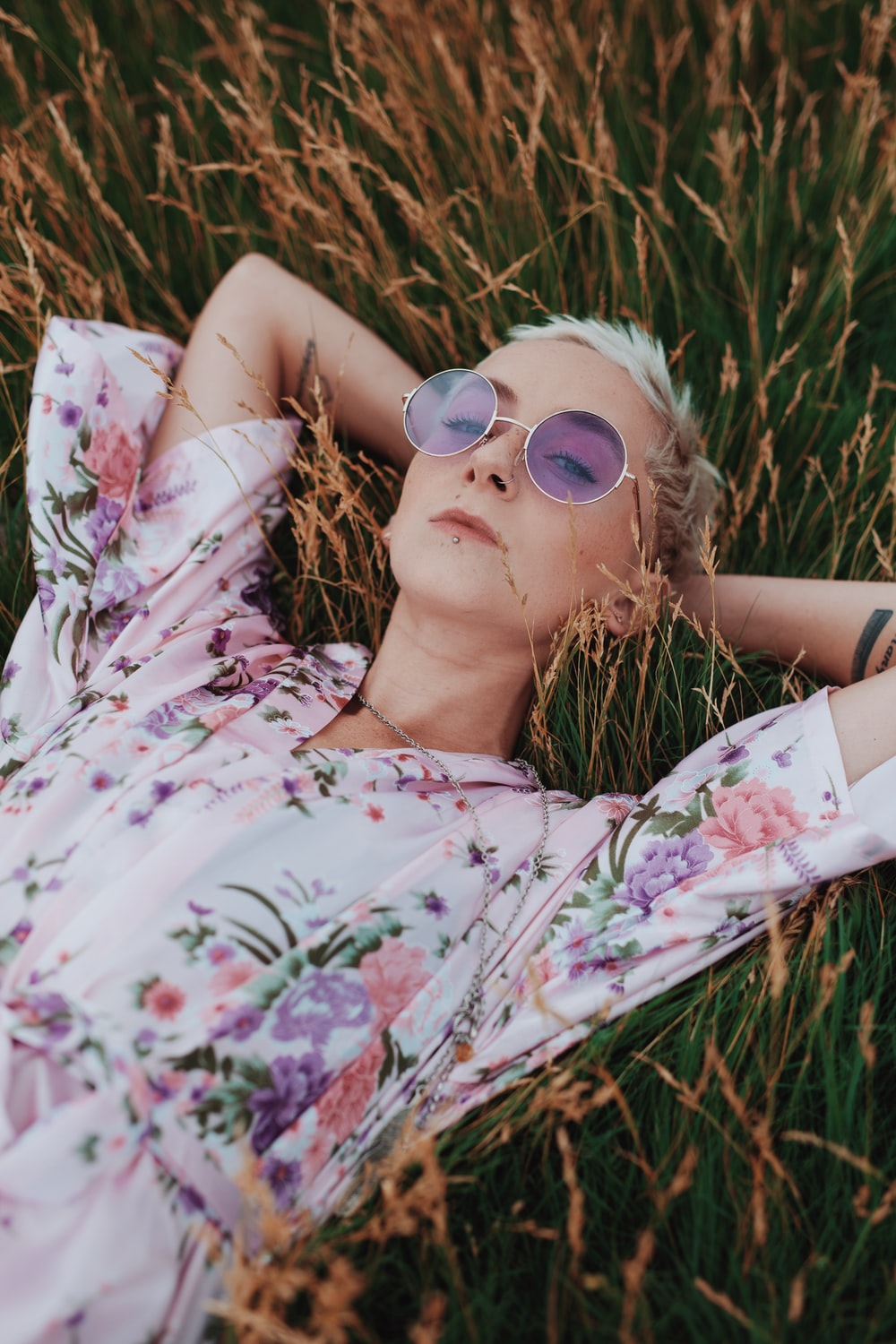 woman in white floral dress lying on grass field
