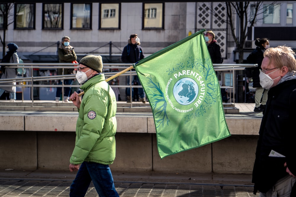 man in green jacket holding green flag