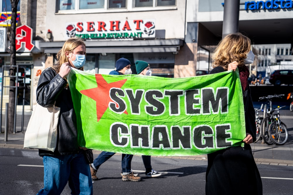 woman in black jacket holding green banner