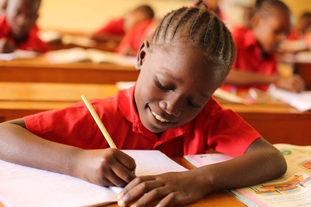 boy in orange shirt writing on white paper