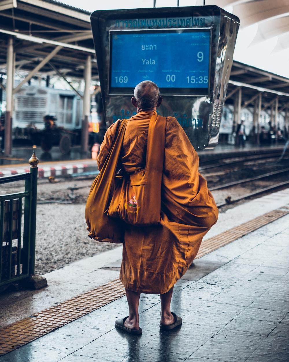 man in brown thobe walking on sidewalk during daytime