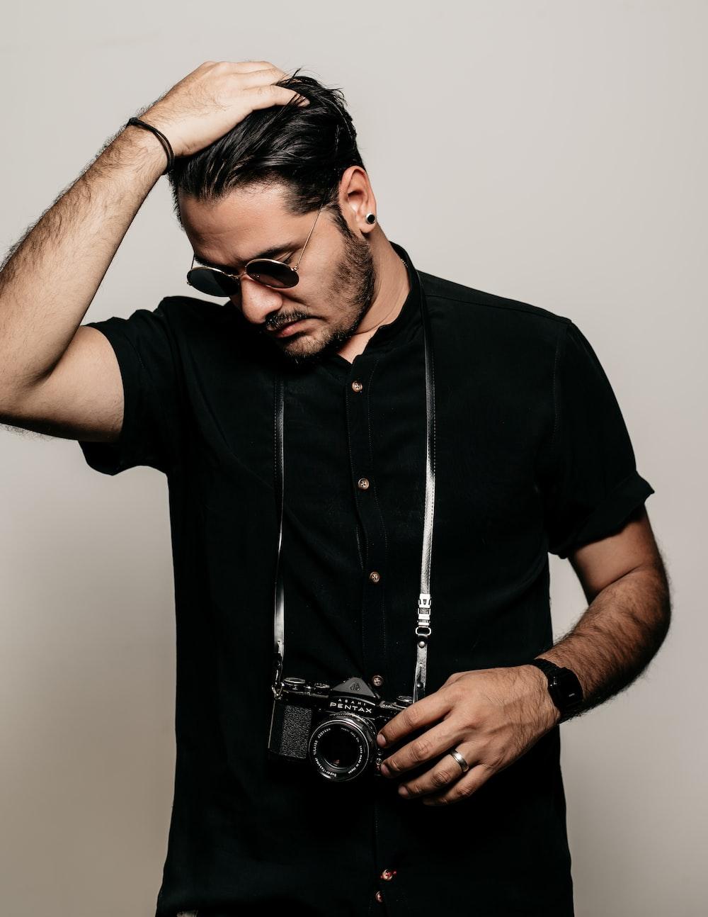 man in black button up shirt holding black dslr camera