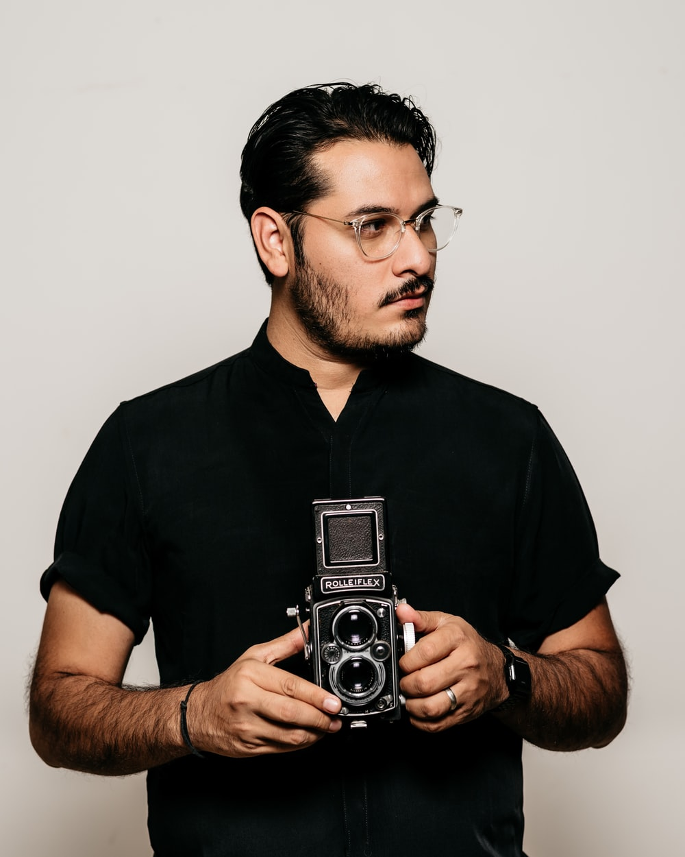 man in black crew neck t-shirt holding silver camera
