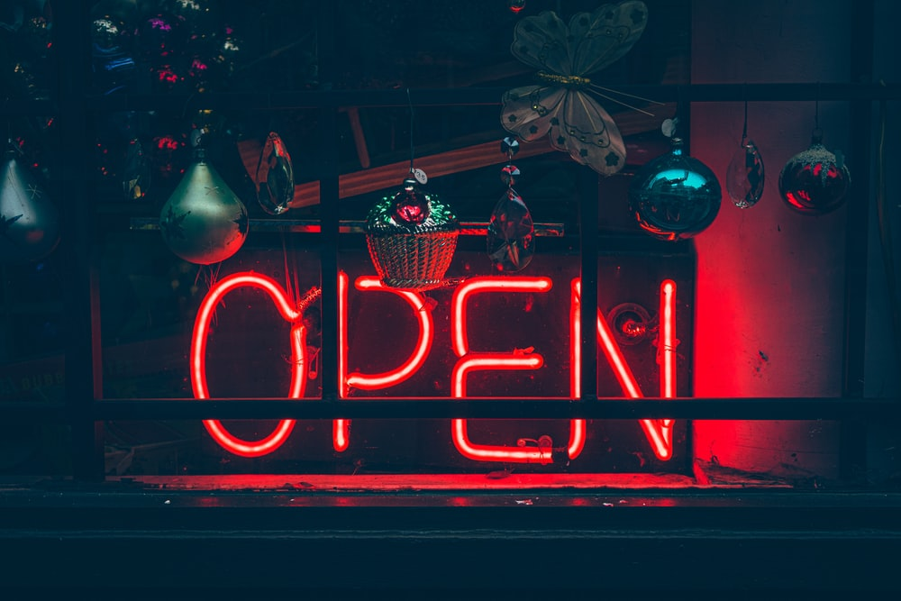 red and white open neon signage