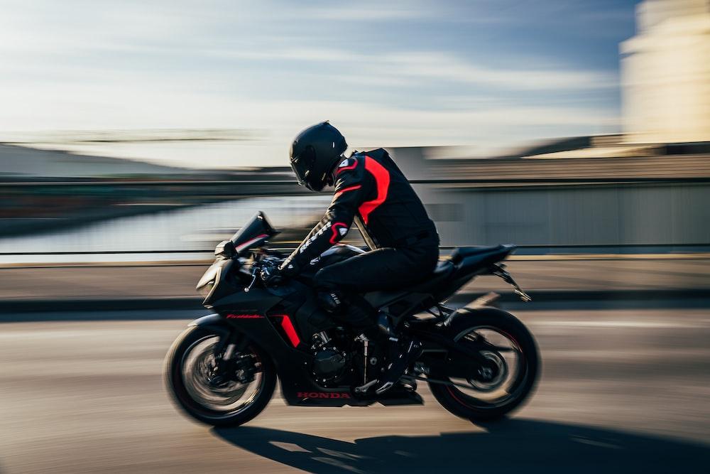 man in black helmet riding black sports bike on road during daytime