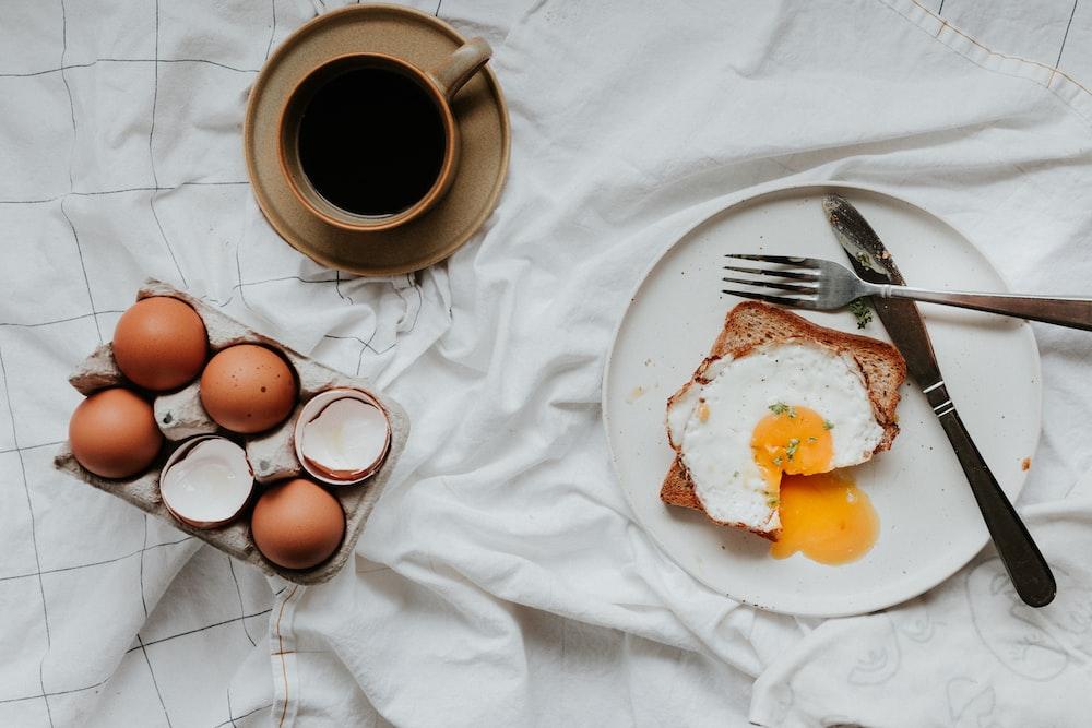 egg on white ceramic plate beside stainless steel fork and knife