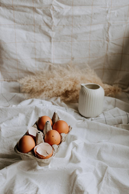 brown eggs on white textile