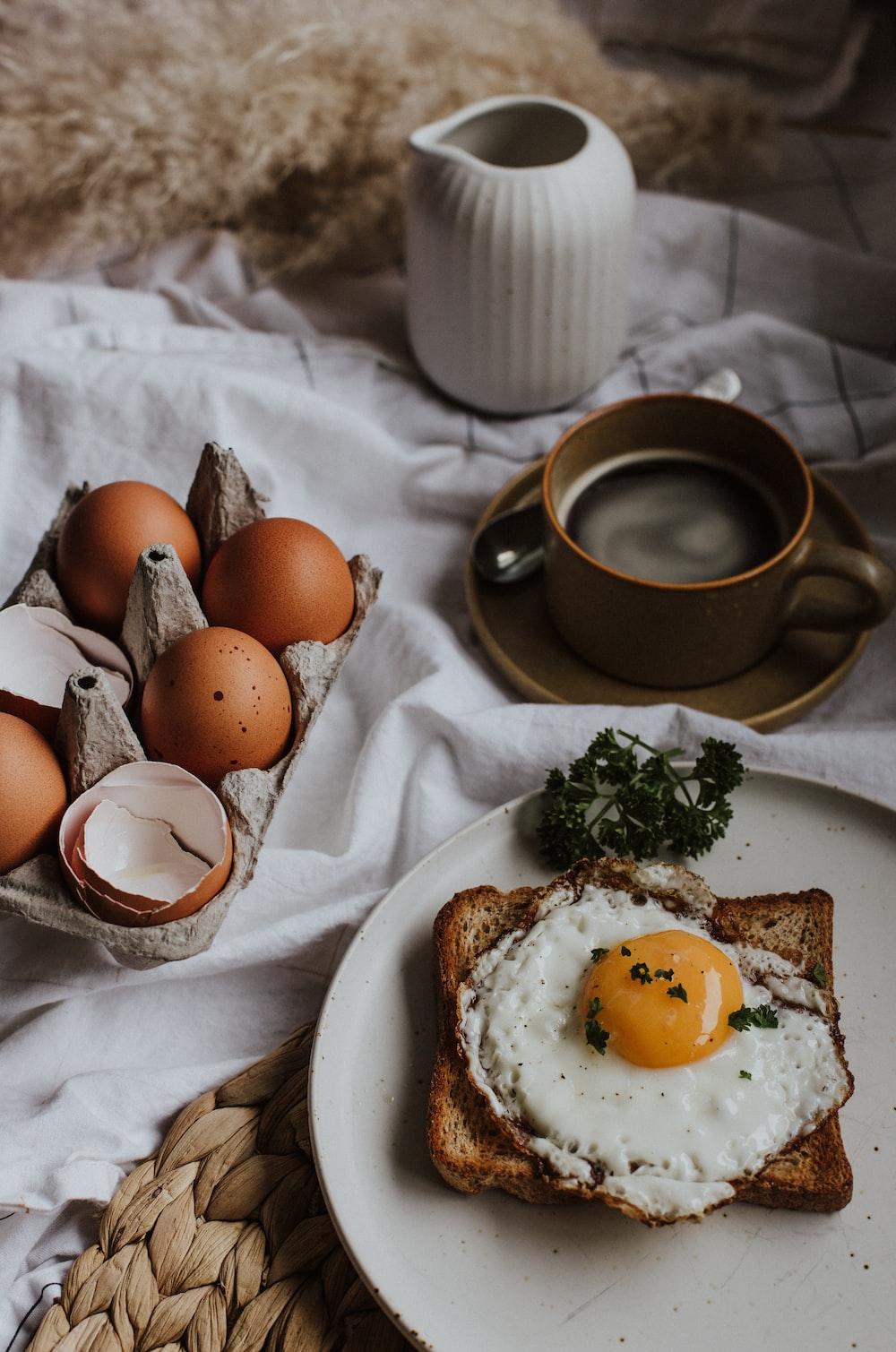 three eggs on white ceramic plate beside brown ceramic mug