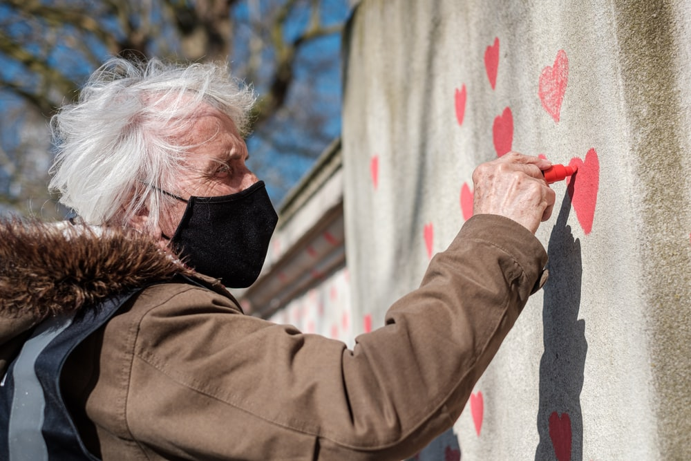 man in brown jacket holding red paint on white wall