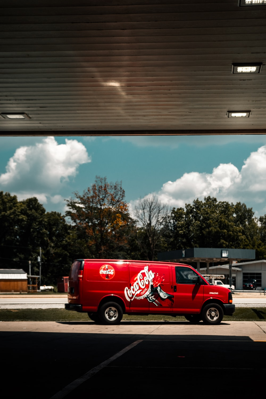 red van parked on parking lot during daytime