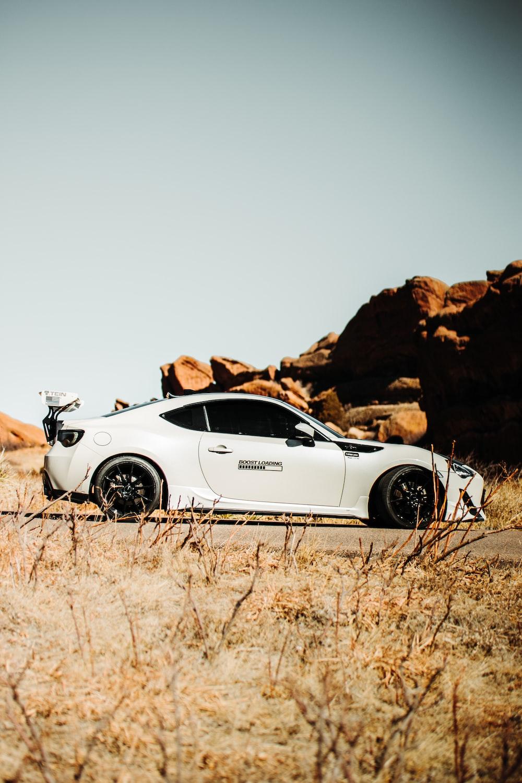 white porsche 911 on brown field during daytime