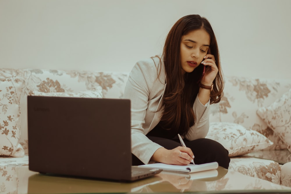 woman in white long sleeve shirt sitting on bed using black laptop computer