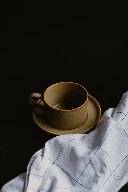 white ceramic mug on white textile