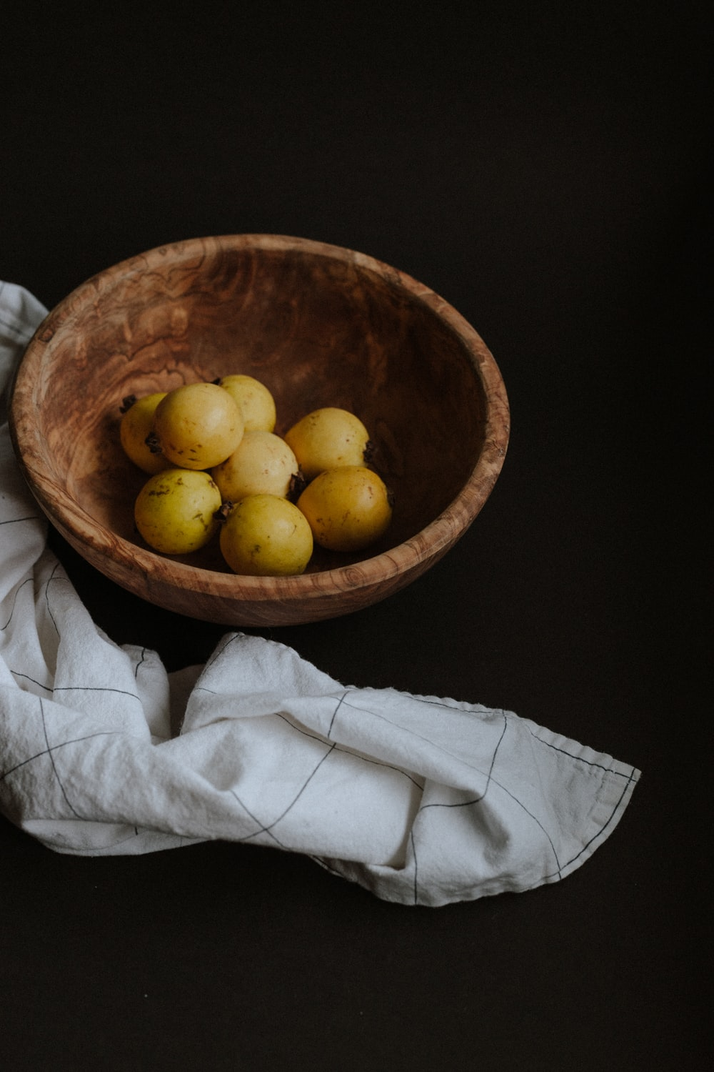 yellow round fruits on brown wooden bowl