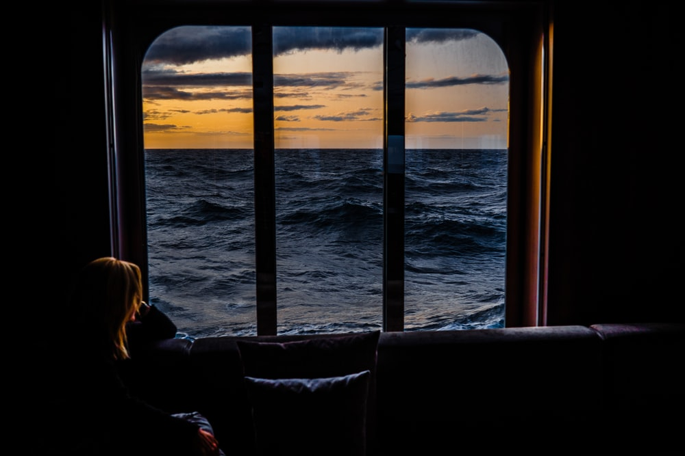 woman sitting on couch looking at the sea during sunset