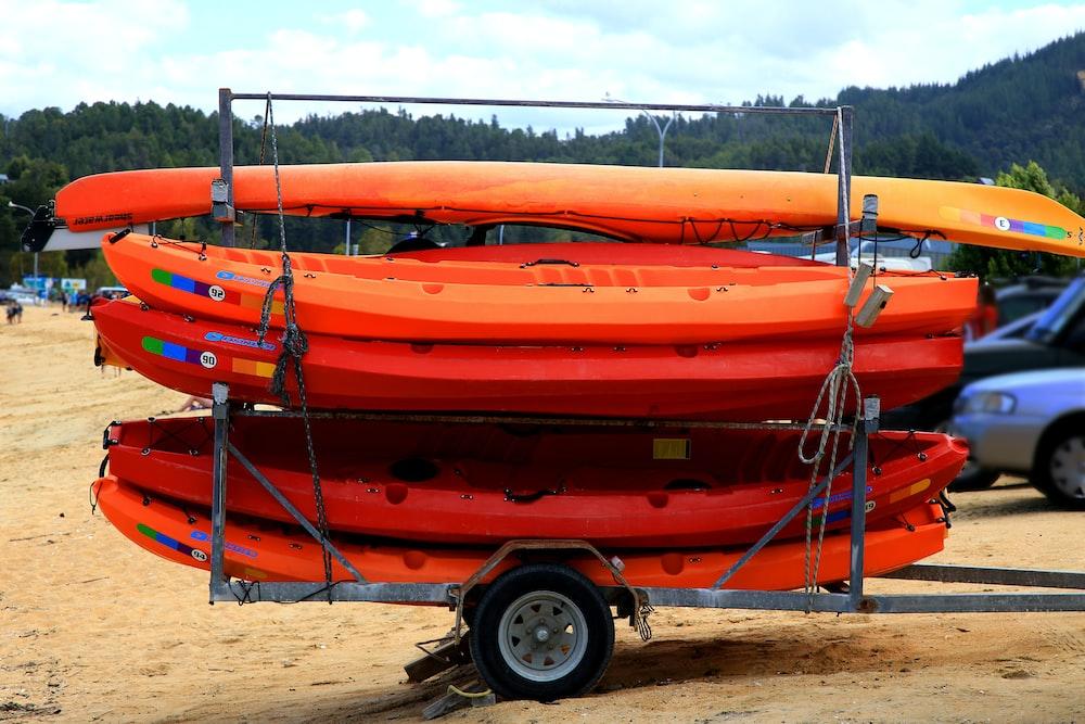 orange and black kayak on brown sand during daytime