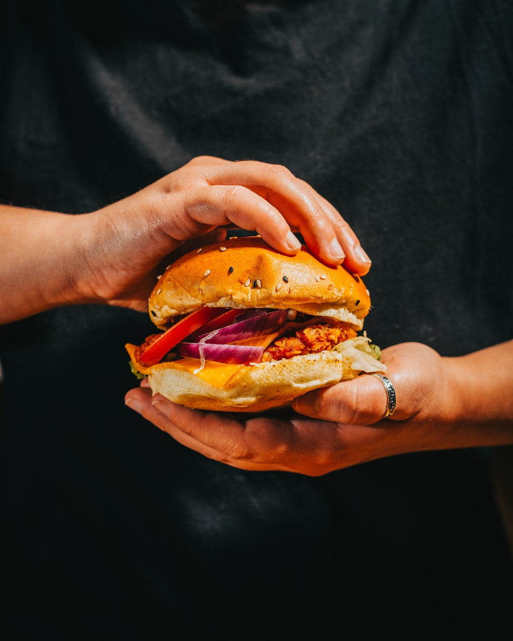 person holding burger with tomato and lettuce