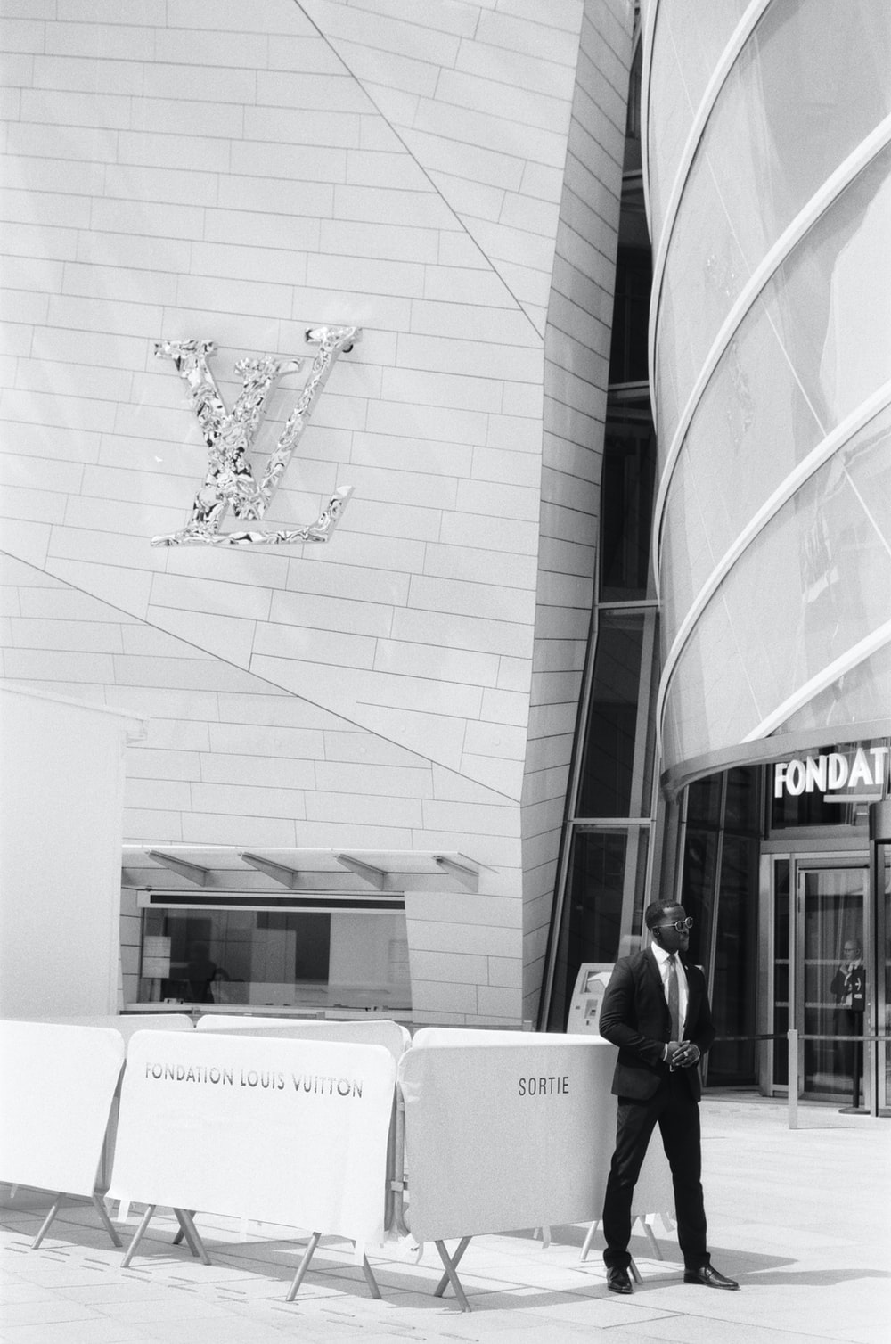 grayscale photo of man in black jacket standing beside building