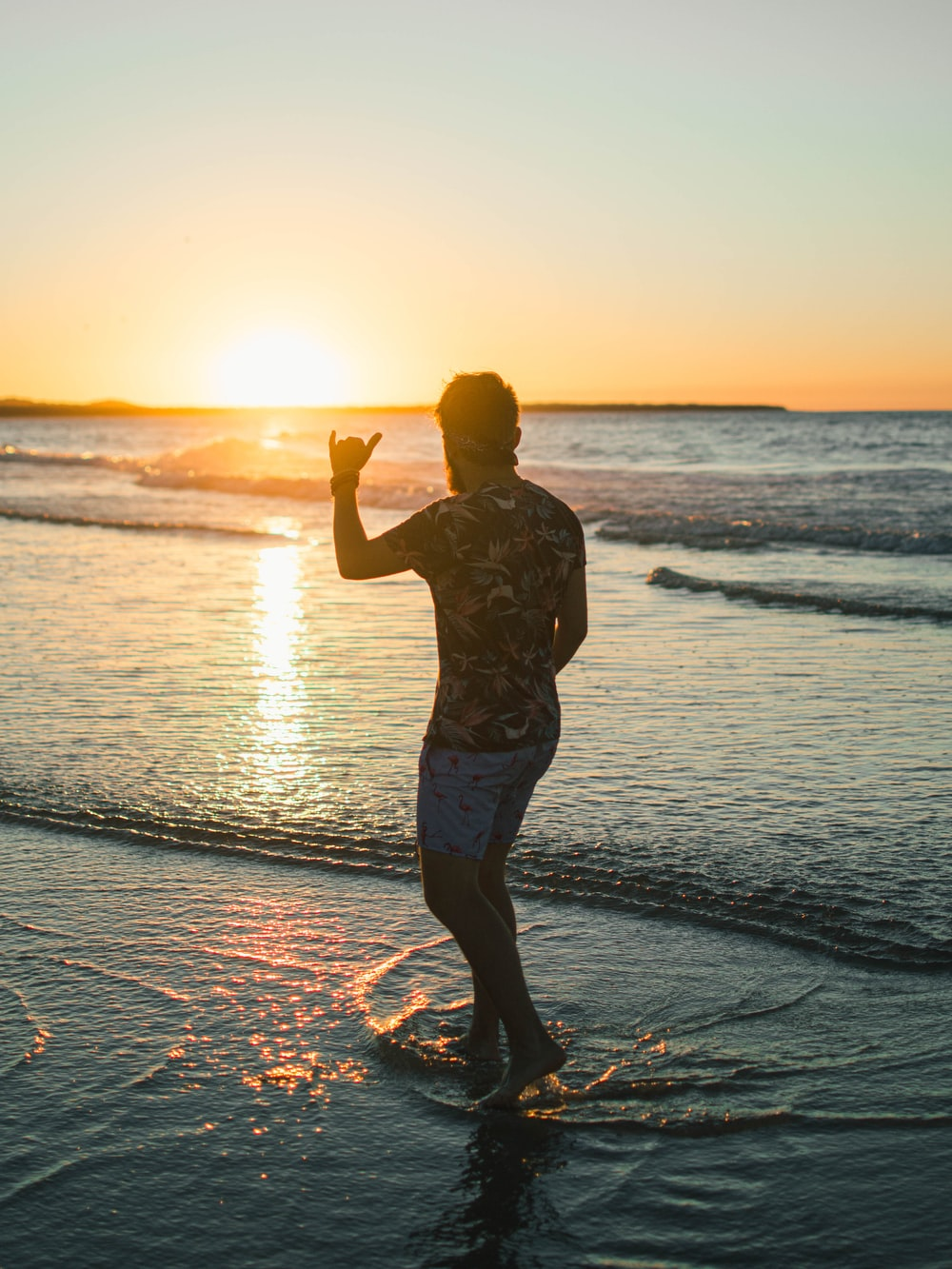 man in black and white floral shirt standing on beach during sunset