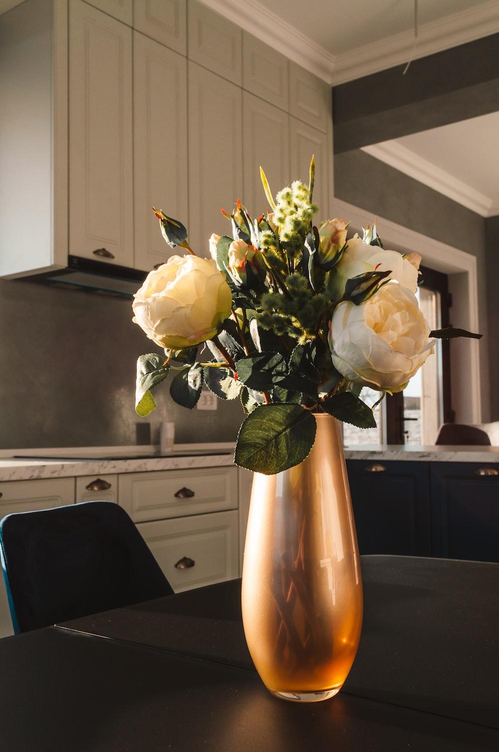 white roses in yellow vase