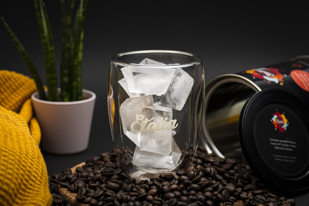 clear glass mug on coffee beans