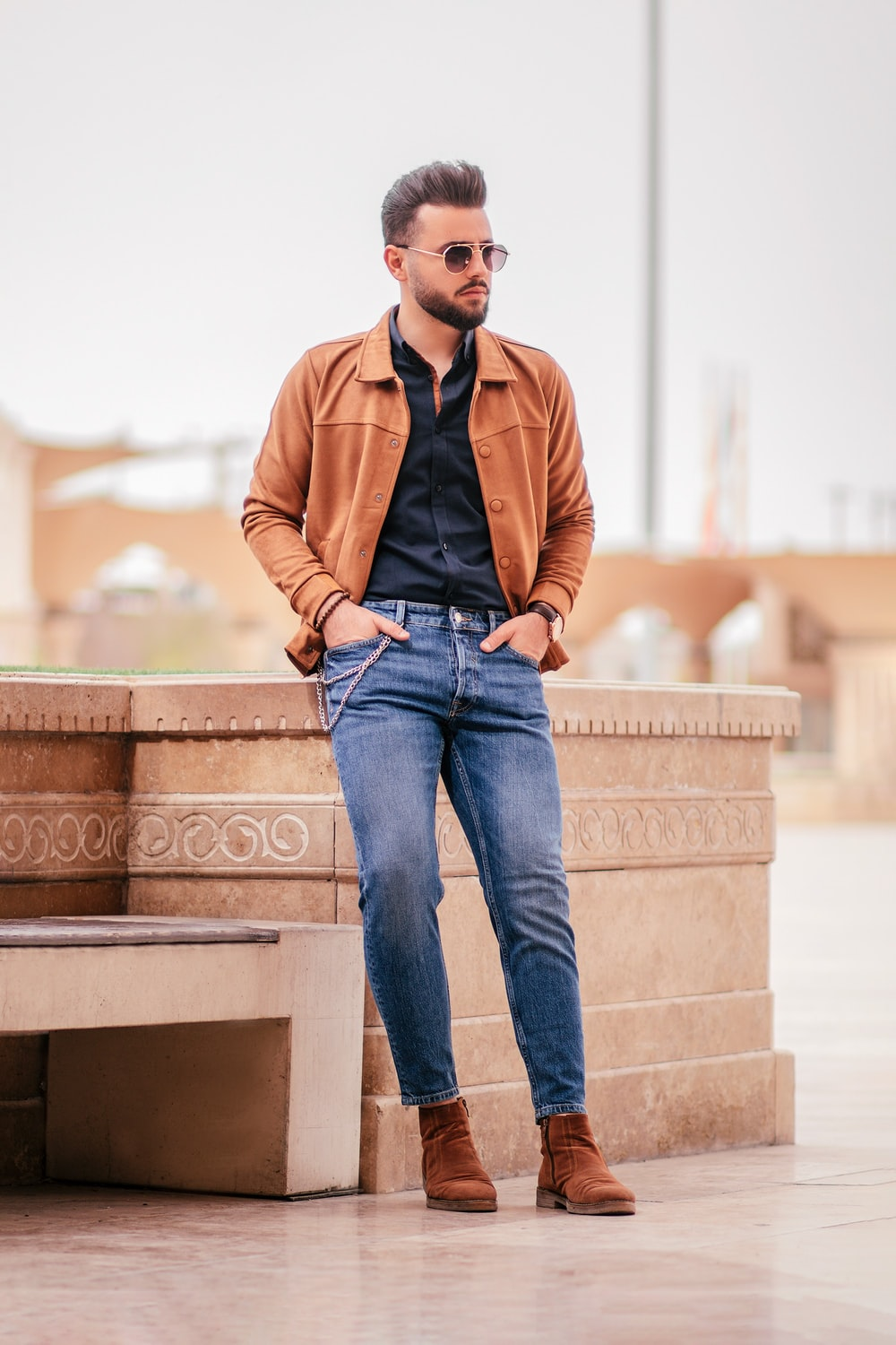 man in brown jacket and blue denim jeans sitting on brown concrete bench during daytime