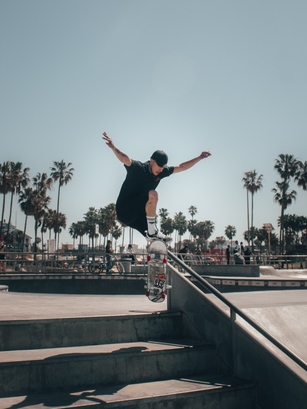 man in black tank top and black pants doing stunts on gray concrete stairs during daytime