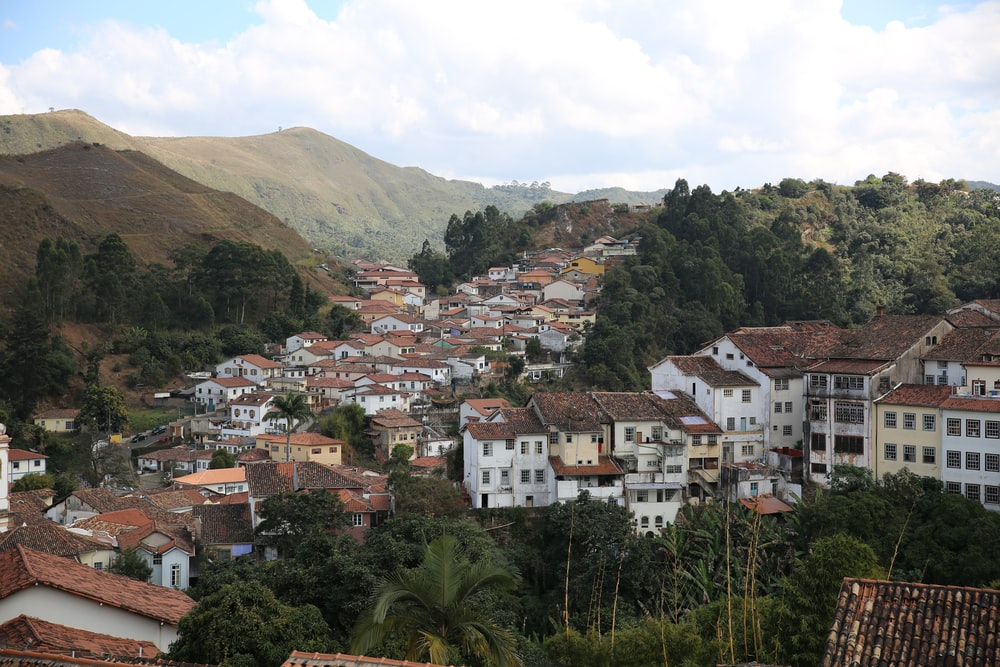 white and brown concrete houses near green trees and mountain during daytime