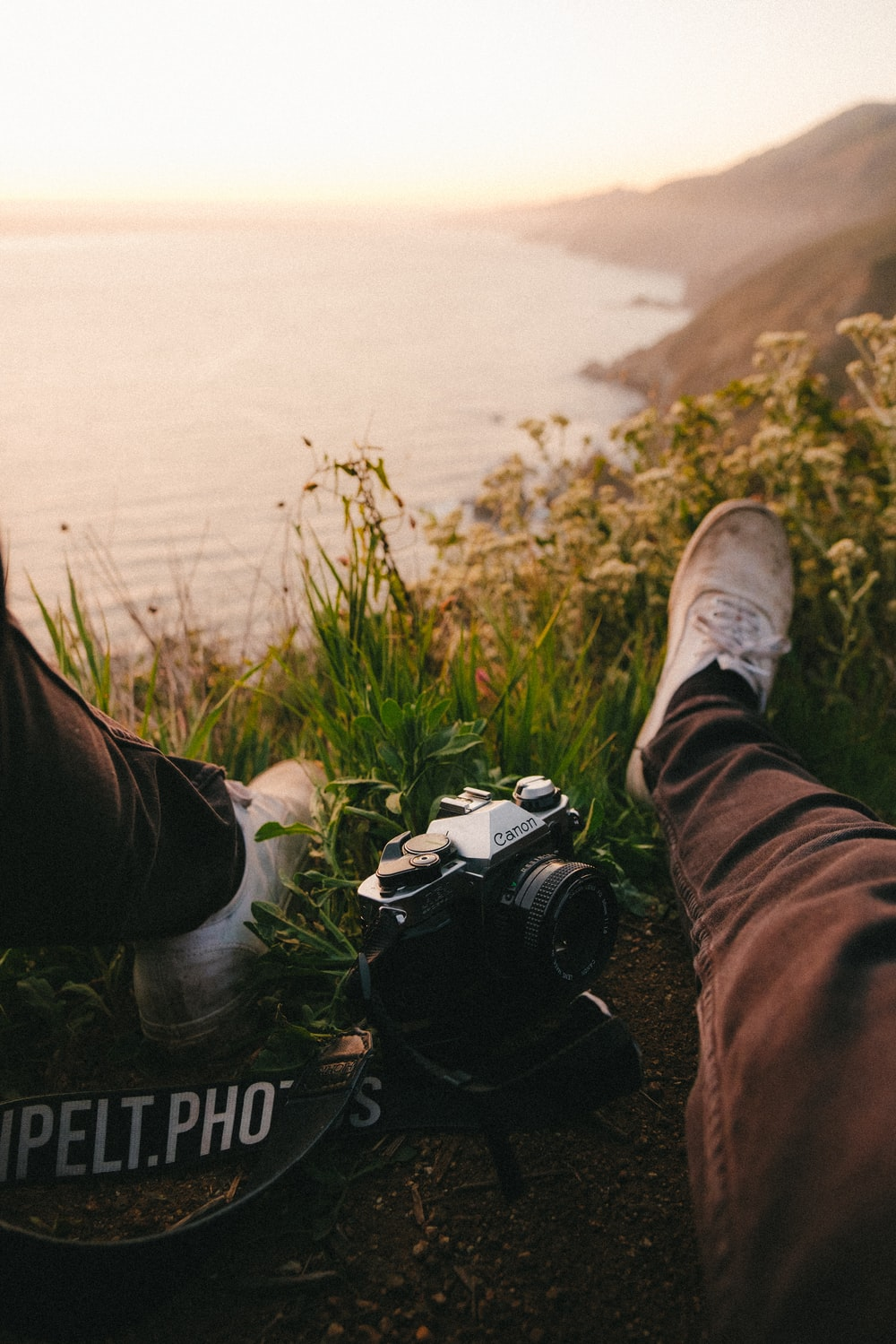 person in black pants and white sneakers sitting on grass field with black and white dslr